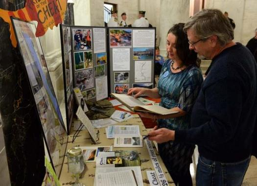 Amanda Pitzer, director of Friends of the Cheat, talks with Charleston resident Paul Dalzell about the quality of the state's water during the West Virginia Environmental Council's annual E-Day at the state Capitol