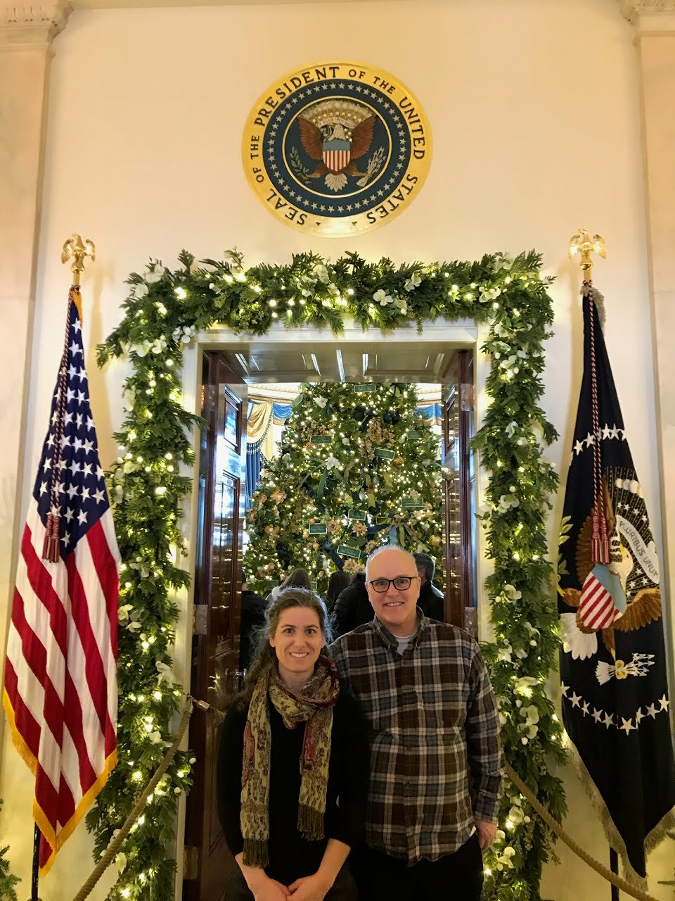 Kristin and Ricky standing under the White House Seal